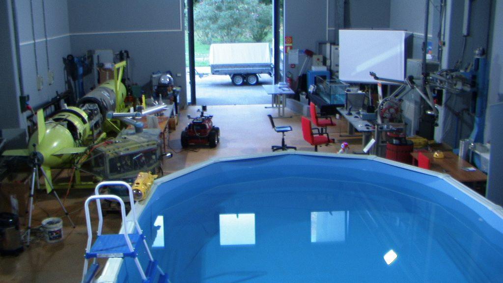 Questa foto è una vista dall'alto della Hall in cui si vedono i robot , la piscina e le postazioni di lavoro.